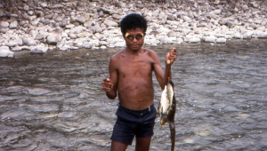 We meet a fisherman with bamboo goggles who has speared an eel and other fish in the shallows.