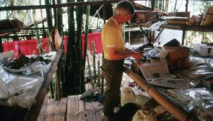 Botanist George Ardent pressing plant specimens at Base Camp C.